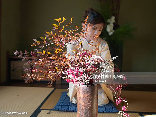 Woman wearing kimono kneeling down and arranging flowers