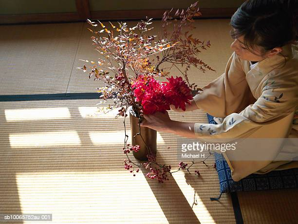 woman wearing kimono organising flower arrangement, side view - ikebana stock pictures, royalty-free photos & images