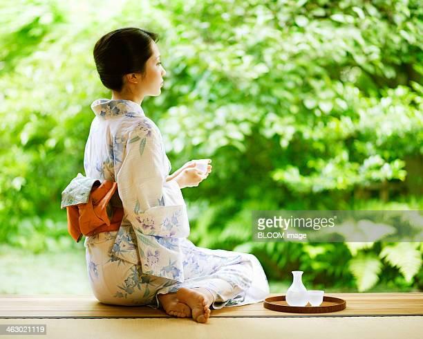 woman wearing kimono sitting on veranda - saki fotografías e imágenes de stock