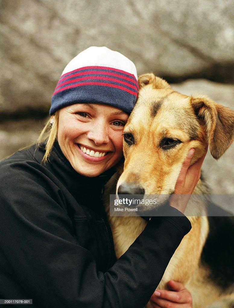 Woman wearing knit cap, hugging dog, portrait : Stock Photo