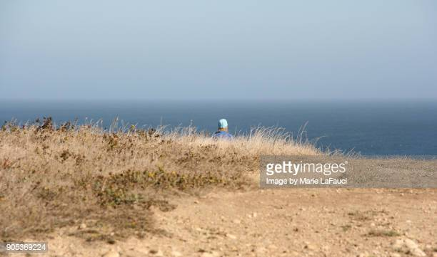Woman wearing knit hat looking at view of the Pacific Ocean