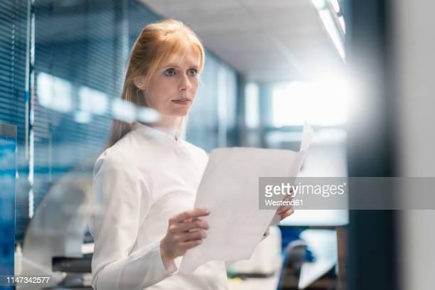 woman wearing lab coat holding plan - wissenschaftlerin stock-fotos und bilder