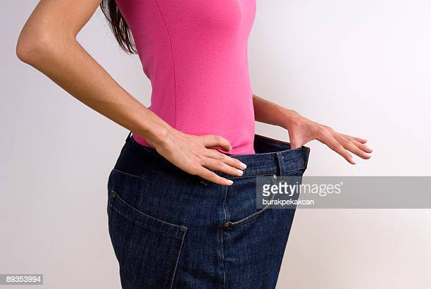 woman wearing large jeans, diet - big fat white women stock pictures, royalty-free photos & images