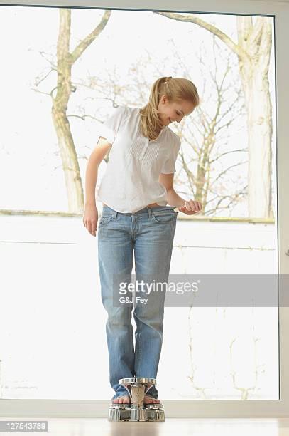 Frau mit großen jeans auf Waage