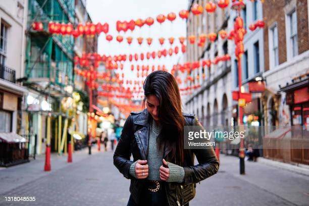 woman wearing leather jacket looking down while standing on street in city - embellished jacket stock pictures, royalty-free photos & images