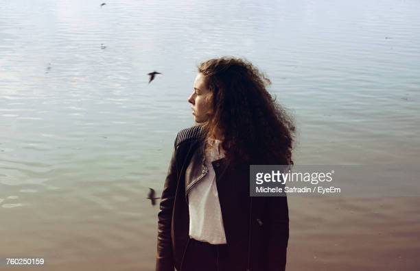 Woman Wearing Leather Jacket While Standing By Lake