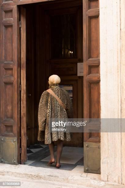Woman wearing leopard fur coat entering church in Rome