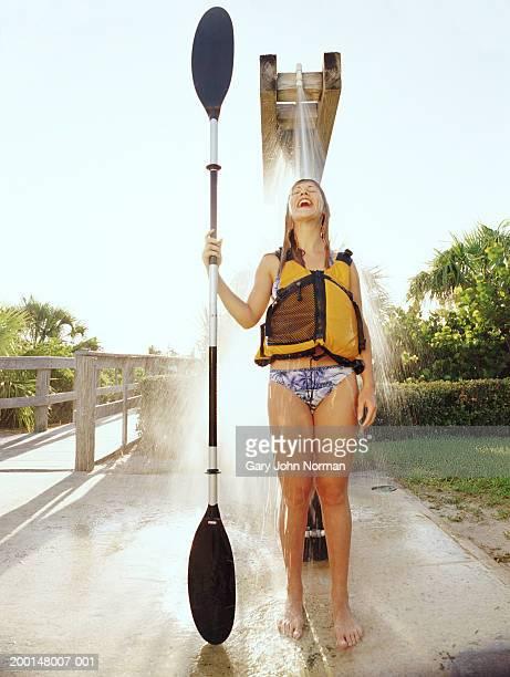 woman wearing life vest, and holding paddle under outdoor shower - frau unter dusche stock-fotos und bilder