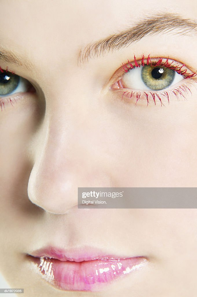 Woman Wearing Lip-gloss and Red Mascara : Stock Photo
