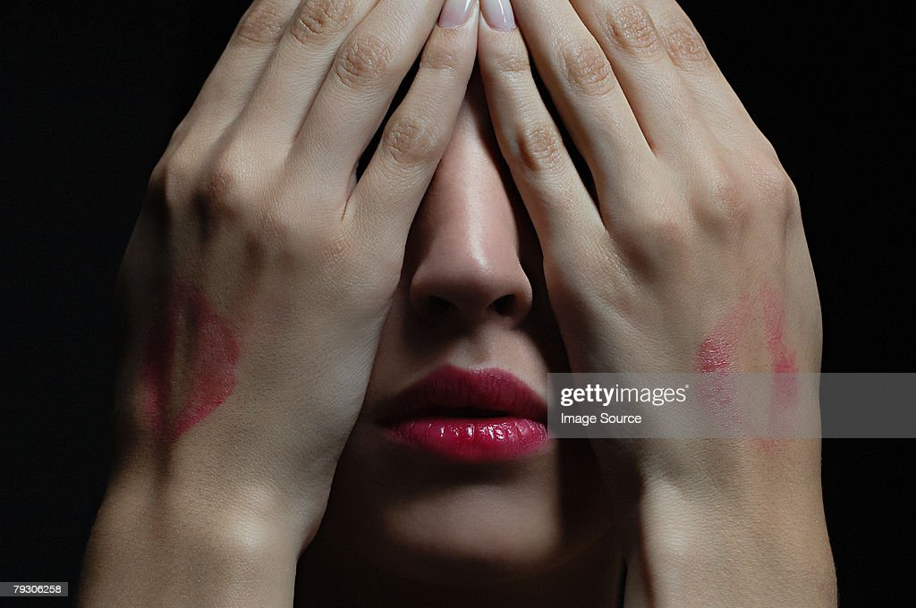 Woman wearing lipstick and covering her face : Stock Photo