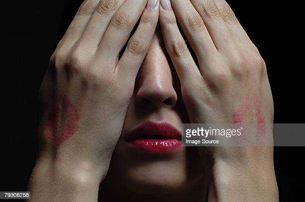 Woman wearing lipstick and covering her face