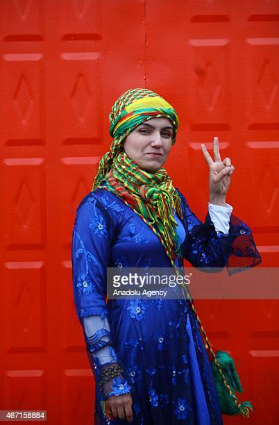 A woman wearing local dress poses in front of a red door during the Newroz celebrations in Diyarbakir southeastern Turkey on March 21 2015 Newroz is...
