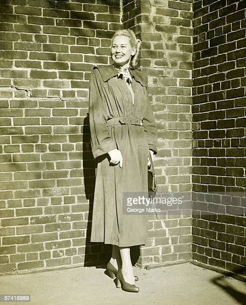 woman wearing mackintosh standing at brick wall outdoors, (b&w) - vintage raincoat stock photos and pictures