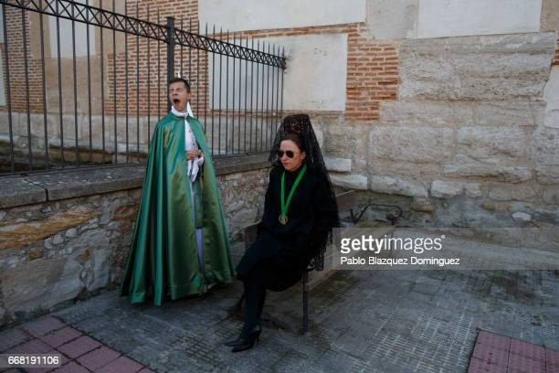A woman wearing 'mantilla' and penitent from the Virgen de la Esperanza brotherhood wait for the start of a procession on April 13 2017 in Zamora...