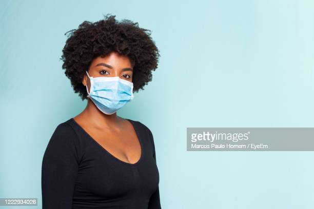 woman wearing mask against blue background - コイリーヘア ストックフォトと画像