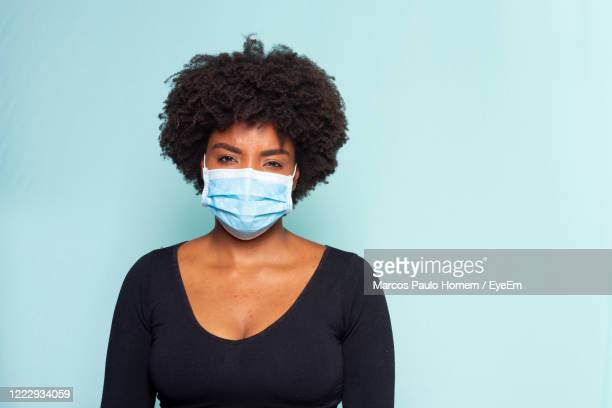 woman wearing mask against blue background - people stock pictures, royalty-free photos & images