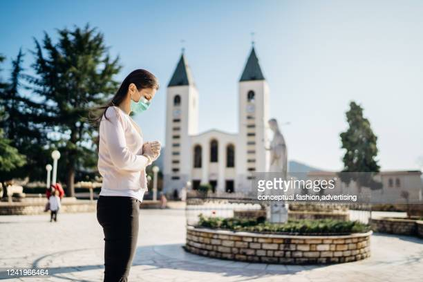 woman wearing mask and gloves praying to god due to novel coronavirus covid-19 outbreak in medjugorje.woman in emotional stress and pain.christianity.strong religion,faith and hope concept - pilgrimage stock pictures, royalty-free photos & images
