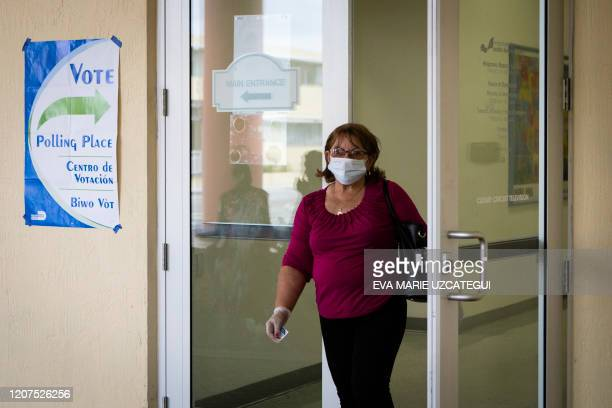 A woman wearing mask and protective gloves leaves after cast her vote during the Florida Democratic primary election at MiamiDade Public Library...