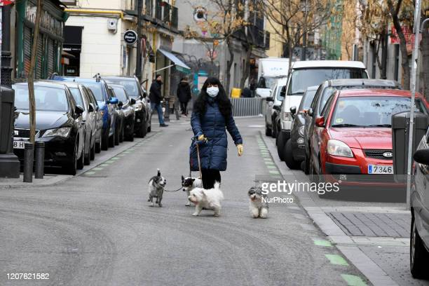 A woman wearing mask as a precaution against the coronavirus with her neighbors' dogs in Madrid Spain on March 18 2020