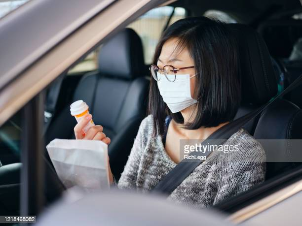 woman wearing mask at drive-through pharmacy - prescription medicine stock pictures, royalty-free photos & images