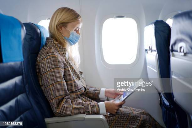 woman wearing mask inside airplane - aeroplane stock pictures, royalty-free photos & images