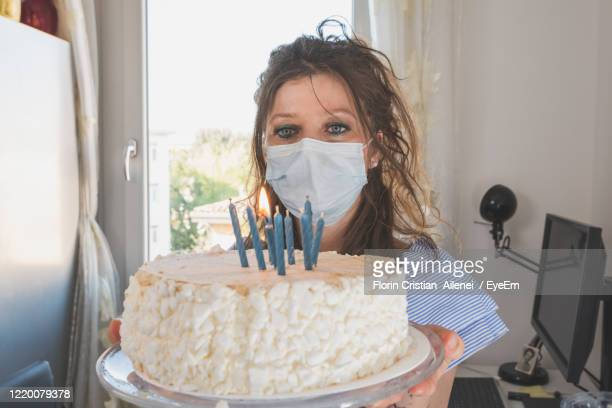 woman wearing mask looking at birthday cake - in flames i the mask stock pictures, royalty-free photos & images