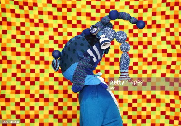 Woman wearing mask made of blue socks,vivid checks color background,side view