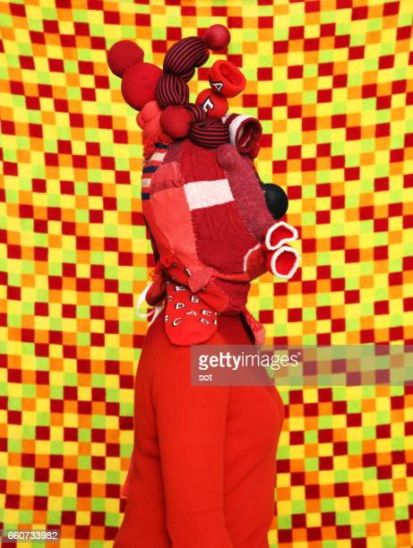 Woman wearing mask made of red socks,vivid checks color background,side view