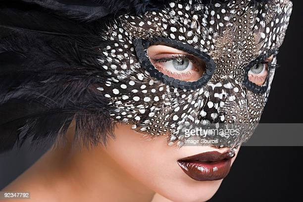 Woman wearing mask of feathers