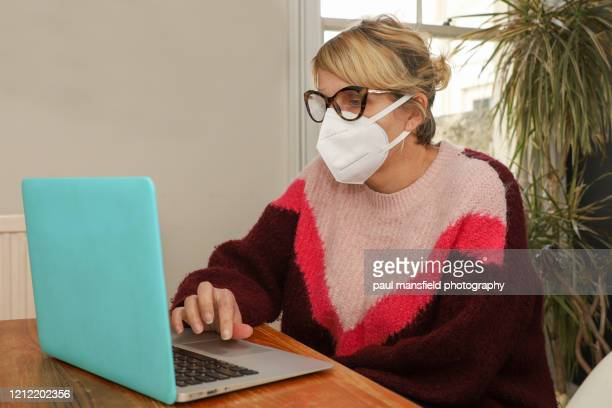 a woman wearing mask self-isolates at home - isolation stock pictures, royalty-free photos & images