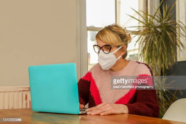 a woman wearing mask self-isolates at home - remote location stock pictures, royalty-free photos & images