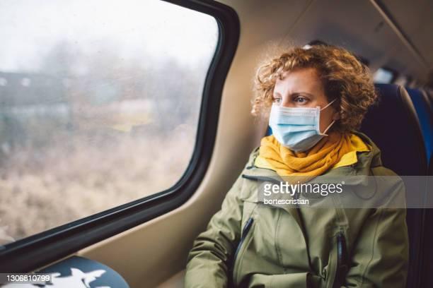 woman wearing mask sitting in train - bortes stockfoto's en -beelden