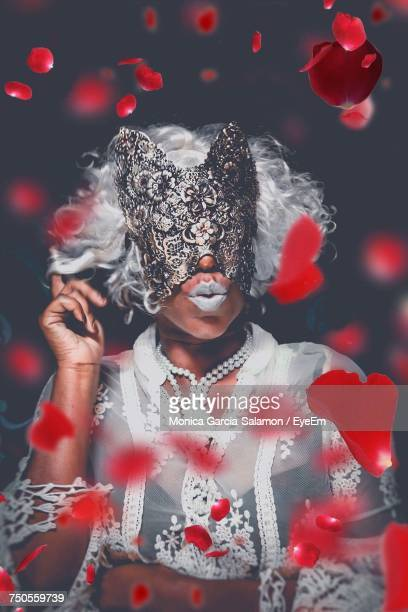 Woman Wearing Mask Standing Against Black Background