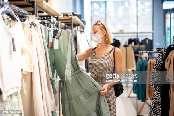 woman wearing mask standing in clothing store - clothing stock pictures, royalty-free photos & images