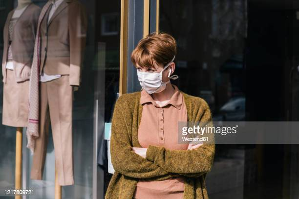 woman wearing mask standing in front of her closed clothing store - essential workers stock pictures, royalty-free photos & images