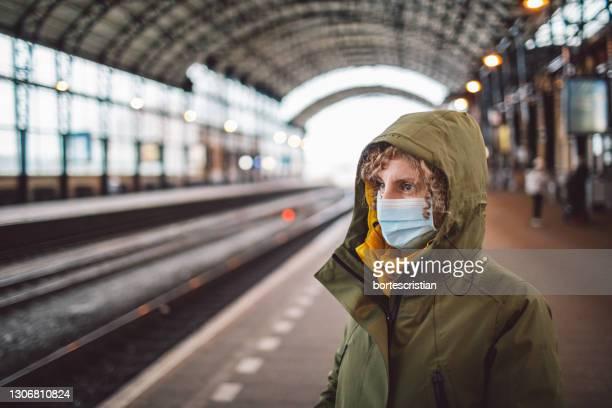 woman wearing mask standing on platform - bortes stockfoto's en -beelden