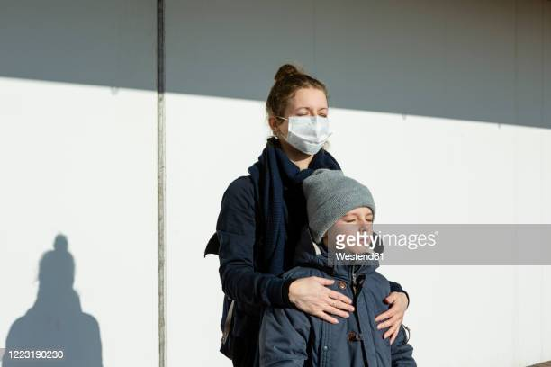 woman wearing mask standing with son in front of a white wall, eyes closed - bronzage masque photos et images de collection