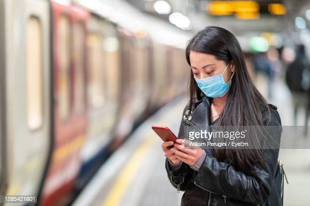 woman wearing mask using smart phone on railroad station platform - london underground stock pictures, royalty-free photos & images