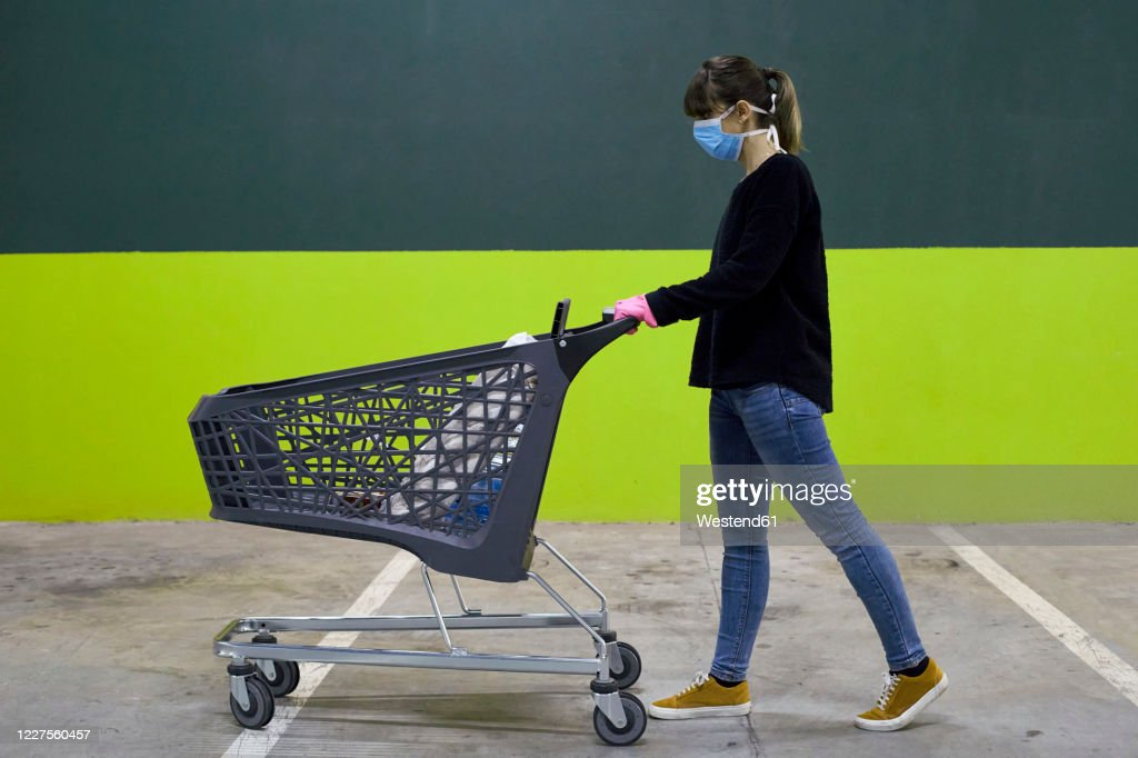 Woman wearing mask walking with shopping cart against wall : Stock Photo