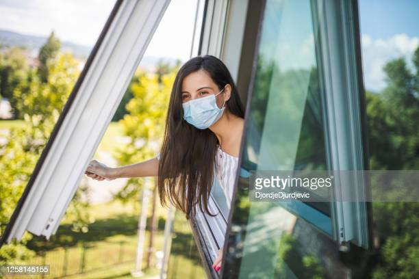 woman wearing medical face mask, staying home for safety and looking through window during coronavirus pandemic - window stock pictures, royalty-free photos & images
