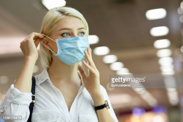 woman wearing medical mask in shopping center - disposable stock pictures, royalty-free photos & images