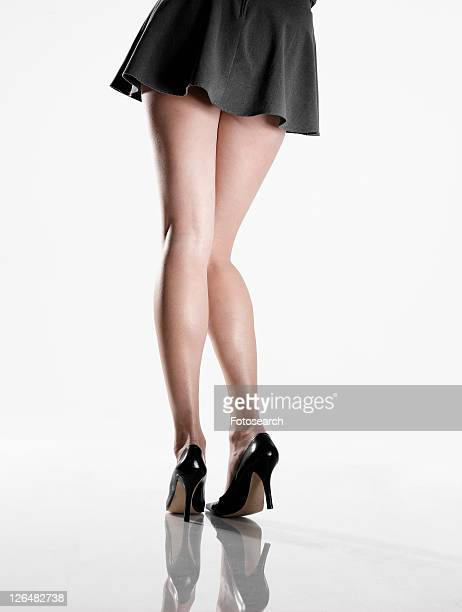 woman wearing mini skirt and high heels (low section, rear view) - mini skirt ストックフォトと画像