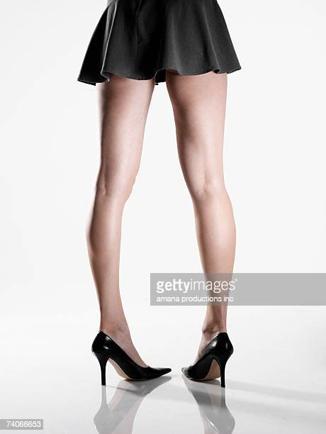 woman wearing mini skirt and high heels (low section, rear view) - high heels short skirts stock pictures, royalty-free photos & images