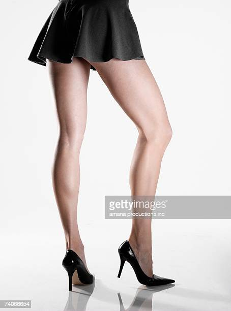 Woman wearing mini skirt and high heels (low section, rear view)