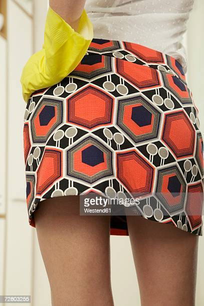 woman wearing mini skirt and rubber gloves, mid section - minirok stockfoto's en -beelden