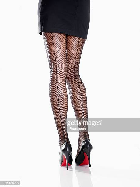 woman wearing miniskirt and stilettos (low section, rear view) - fishnet stockings stock pictures, royalty-free photos & images