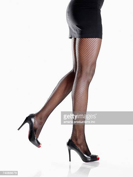 woman wearing miniskirt and stilettos (low section) - fishnet stockings stock pictures, royalty-free photos & images