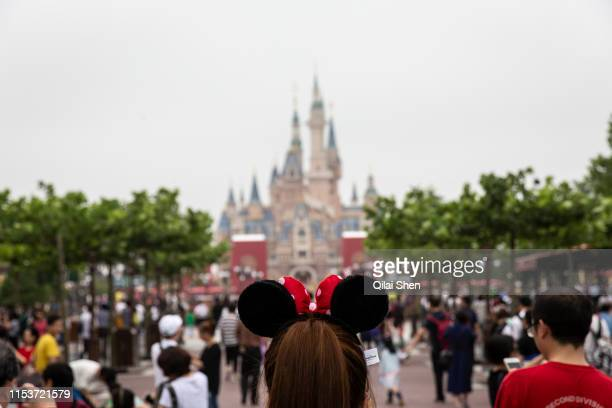 A woman wearing Minnie Mouse ears walks through Walt Disney Co's Shanghai Disneyland theme park towards the iconic castle during a trial run ahead of...
