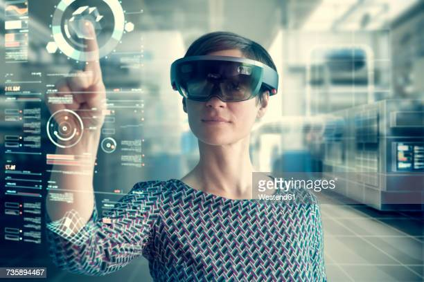 woman wearing mixed reality smartglasses touching transparent screen - realtà aumentata foto e immagini stock