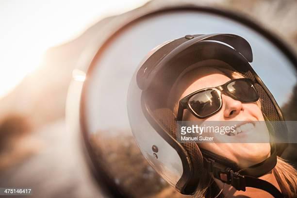Woman wearing motorbike helmet and sunglasses
